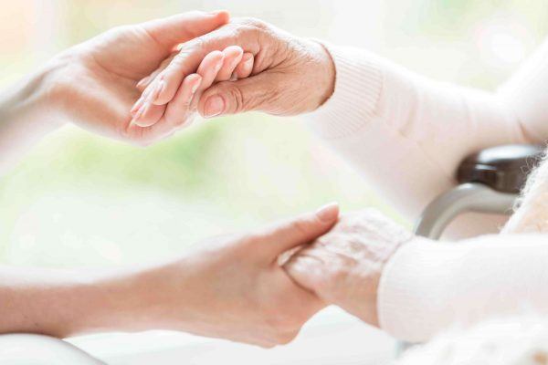 Geriatrics: Close-up of a young female chiropractor and a senior lady holding hands.